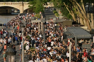 Parisians eat and drink on the terraces of food stalls on the banks of the river Seine