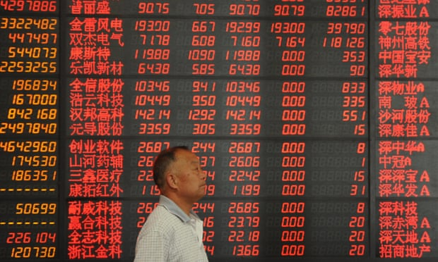 A Chinese investor walks past a screen displaying prices of shares at a stock brokerage house in Fuyang city.