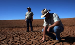 Men inspecting drought-affected soil.