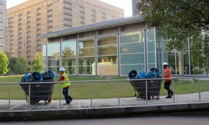 Workers remove equipment being used to clean up and dry the $13m Harris County jury assembly building in Houston.