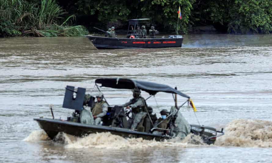 A Colombian navy boat patrols the Arauca river while a Venezuelan navy boat remains anchored on the border between their two countries as seen from Arauquita, Colombia.