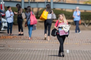 A woman carries a box through the carpark outside the Peterborough headquarters of tour operator Thomas Cook