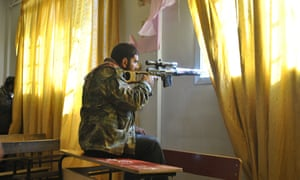 A Syrian rebel aims his rifle inside a classroom at a school in Deir Baalbeh neighbourhood in Homs province in February 2012