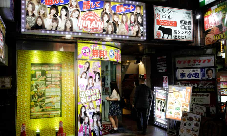 A young woman hovers in the doorway of one of Kabukicho's information centres, which give recommendations for bars and sex shops.