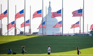 Flags fly at half-staff around the Washington Monument, with the Capitol dome in the background.