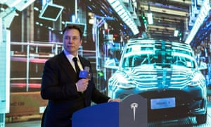 Elon Musk standing at a podium with a microphone, with a backdrop photograph of Teslas on the production line behind him