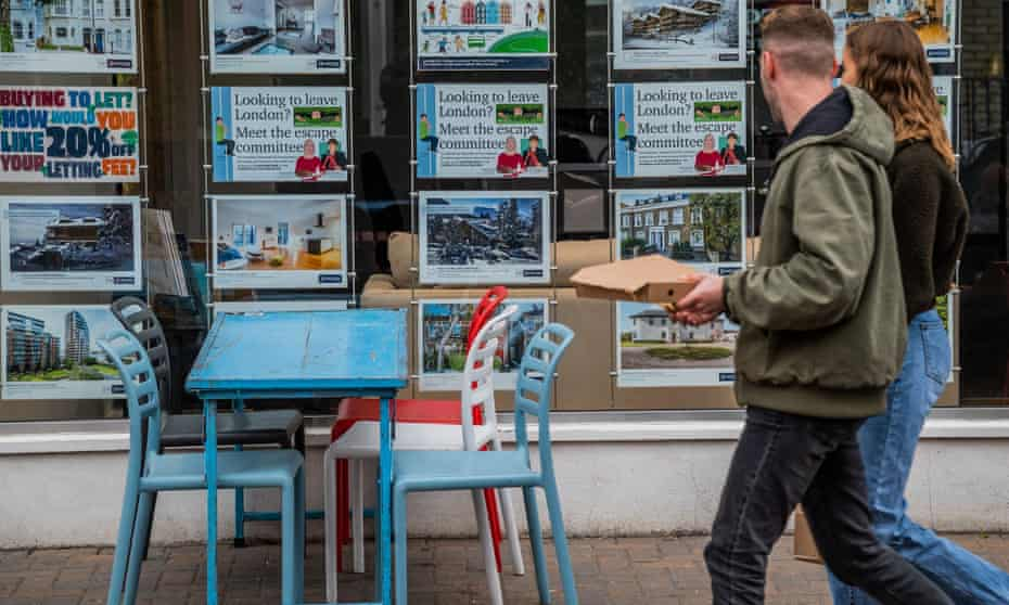 young couple walk past estate agent's window in clapham, south london