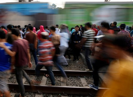 Commuters walks along railway tracks while transferring to another train at Tanah Abang train station in Jakarta