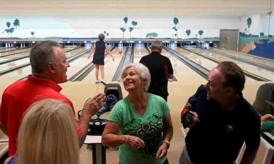 People elbow bump while bowling at Spanish Springs Town Square, in The Villages, Florida, in March.