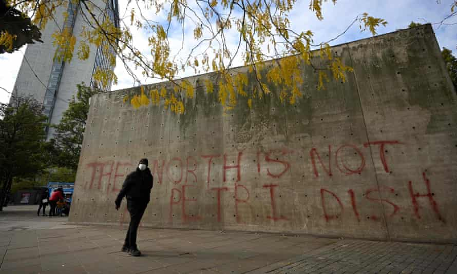 A man wearing a face mask walks past graffiti in Picadilly Gardens, central Manchester.