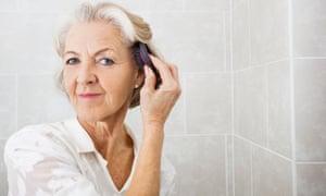Senior woman brushing hair in bathroom