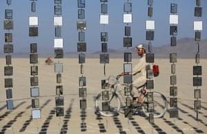 Festivalgoer Austin Cable rides past an art installation