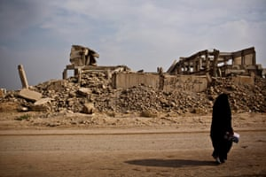 A woman walks passed a destroyed university building in Hamam al-Alil, Mosul, in September 2017