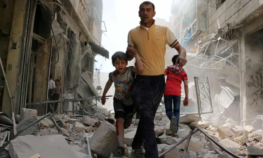 Syrians in the rebel-held neighbourhood of Hayy Aqyul in Aleppo after an airstrike.