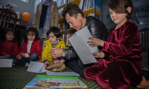 Qanbar Ali Zareh sits with his daughters at a junior book club in Kabul