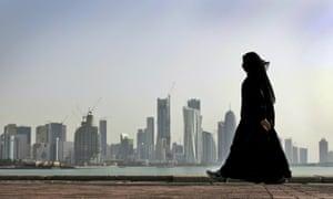 A Qatari woman walks in front of the city skyline in Doha, Qatar