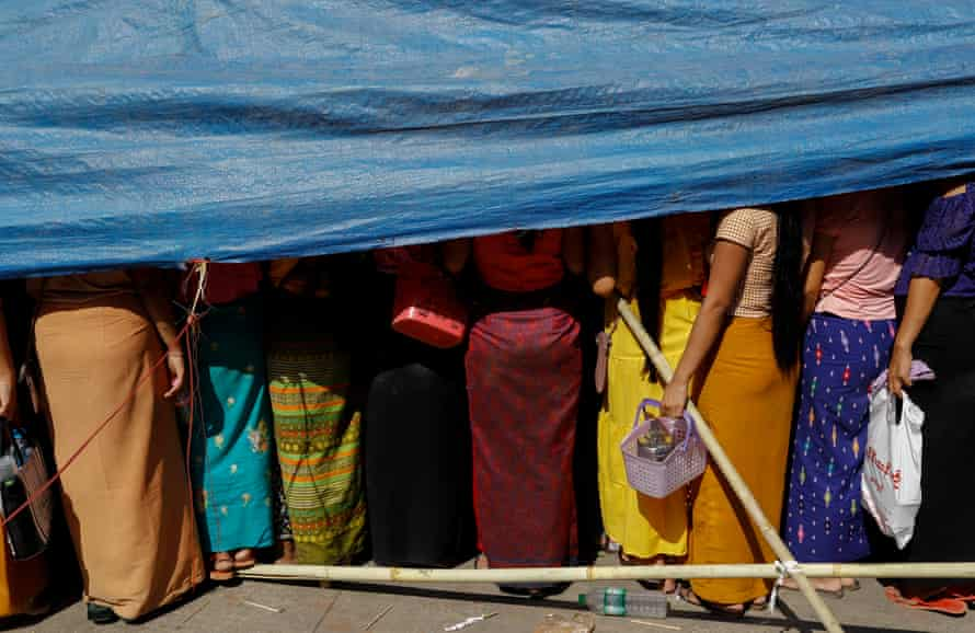 Workers gather under temporary shelter as they demand labor rights outside a garment factory on the outskirts of Yangon, Myanmar, 26 March 2020.