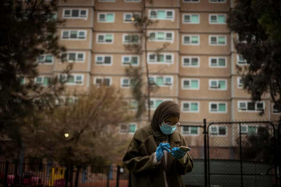 Hiba Shanino checks her mobile phone while wearing a face mask and gloves.