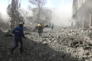 The Syrian Civil Defence group, known as the White Helmets, run to help survivors from a street that was attacked by airstrikes