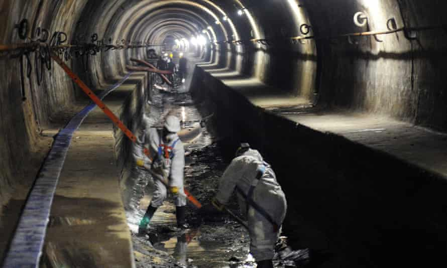 Sewage workers clean a sewer pipe