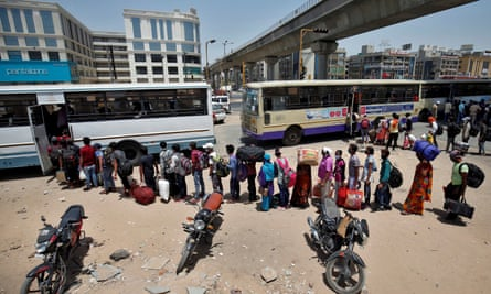 People queue to get on buses to leave the city of Ahmedabad in India as the lockdown is extended.