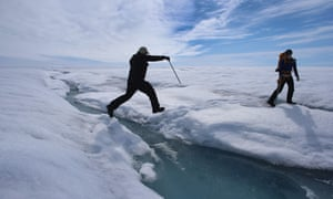 A scientist leaps over water during a trip to the Greenland ice sheet, which saw melting over more than 50% of its surface last year.