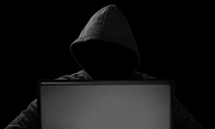 hacker behind notebook laptop