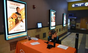 An employee at an empty Regal Cinemas movie theatre table on 15 March in Washington, DC.