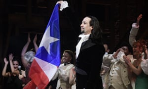 Lin-Manuel Miranda waves a Puerto Rican flag during a standing ovation at the end of Hamilton's premiere in San Juan.