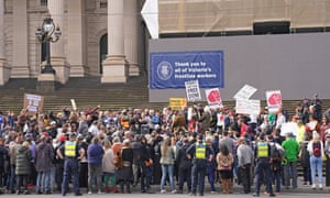 a crowd stands on the steps of Melbourne's parliament house with placards