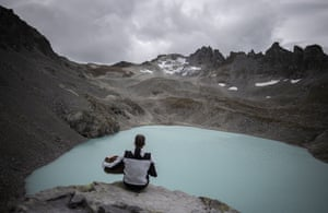 Wangs, SwitzerlandA hiker plays his accordion with view of Wildlake and the Pizol glacier on the sideline of a commemoration for the dying glacier of Pizol mountain, pictured in the background