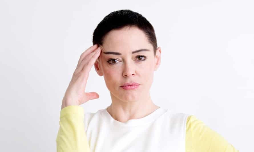 Rose McGowan posing for a portrait, one hand on her temple, wearing a white top with yellow sleeves