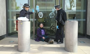 Police officers with a demonstrator who was freed after she had glued herself to the front of the Shell building in London on 15 April.