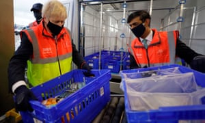 Boris Johnson and Rishi Sunak load produce at Tesco's Erith distribution centre in south-east London last week.