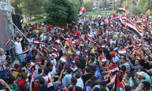 Syrian people celebrate their draw after watching the match on a big screen in a Damascus park.