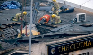 Rescue workers preparing to lift the wreckage of the helicopter from the Clutha pub in central Glasgow.