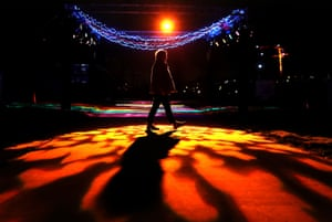 A visitor walks past a light tunnel at an event in Falkirk, UK