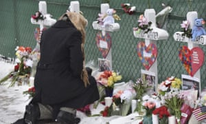A mourners places a flower at the crosses outside of the Henry Pratt Company in Aurora.