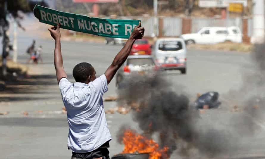 A man carries a pulled down street sign during protests against President Robert Mugabe.