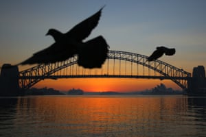 The sun rises behind the Sydney Opera House and the Sydney Harbour Bridge