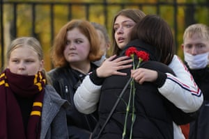 Students comfort each other outside after a shooting on campus at Perm State University in Russia