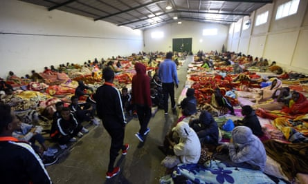 African migrants sitting in a shelter at the Tariq Al-Matar migrant detention centre on the outskirts of the Libyan capital, Tripoli.