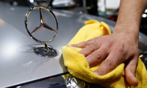 A worker polishing the hood of a Mercedes vehicle.