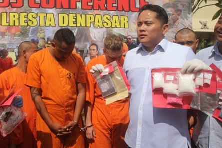 Indonesian policemen present Australians William Cabantog (L) and David Van Iersel (C) to journalists during a press conference at a police station in Denpasar
