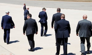 Trump in hat with bald men risking sunburn.