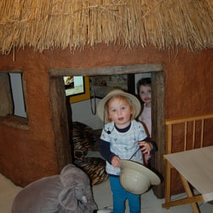 Children play in the reconstructed rondavel house at Gilbert White's House and Gardens, Selborne, Hampshire, UK.