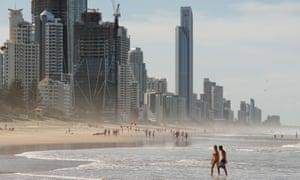 People walk along a Gold Coast beach.