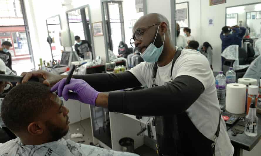 Kevin Sibblies cuts a customer's hair