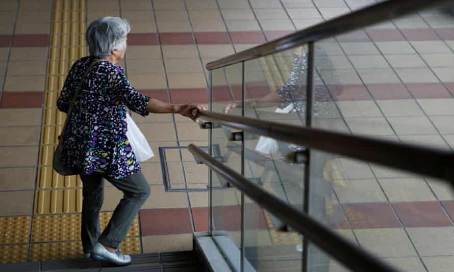 An elderly woman walks down a flight of steps in Akita, Japan