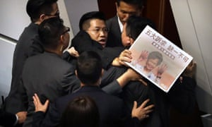 Gary Fan, a pro-democracy lawmaker, is forcibly removed by security officials as he protests during Carrie Lam's speech.